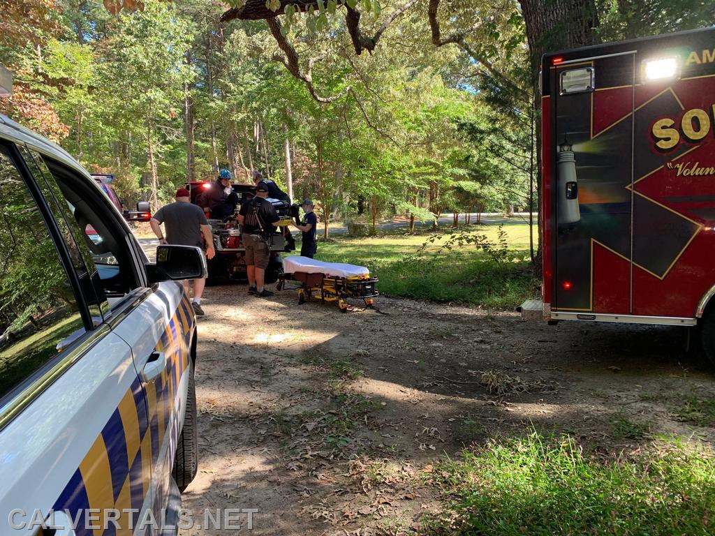 Units arrive back at the paved road after removing the patient from the wooded area.