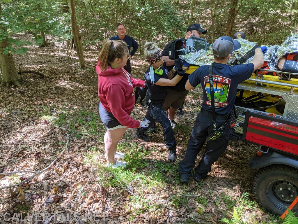 Crews work to secure patient to Gator 3 for transport out of the woods after carrying her up an embankment.